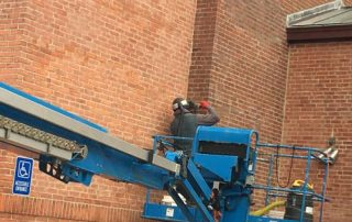 man on lift washing brick wall