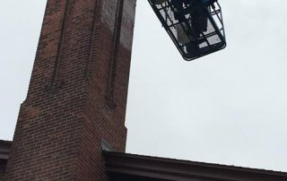 man on lift washing brick chimney