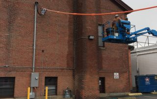 men on a lift cleaning brick bulding