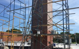 man restoring brick chimney